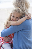 Mother and daughter hugging on sunny beach