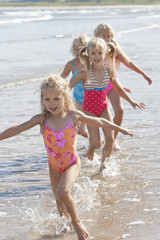 Girls in bathing suits running with arms outstretched in ocean