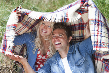 Happy couple holding blanket overhead in sunny field