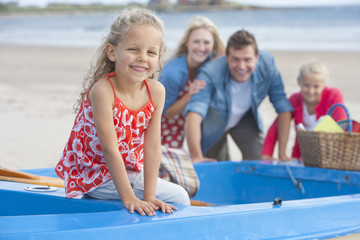 Portrait of smiling family in boat on beach