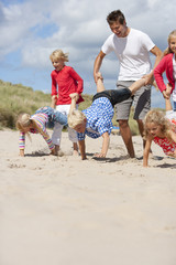 Man and kids playing wheelbarrow race on sunny beach