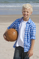 Portrait of smiling boy holding soccer ball on sunny beach