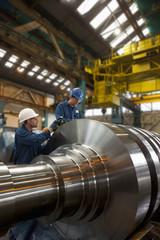 Engineers working on metal machinery