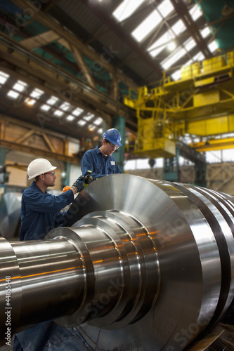 Engineers working on metal machinery
