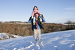 Portrait of father carrying daughter on shoulders in snowy field