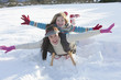 Portrait of smiling mother and daughter laying on sled with arms outstretched in snow