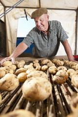 Smiling farmer inspecting potatoes on conveyor belt