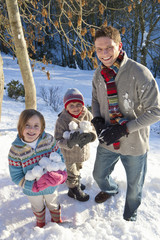 Portrait of smiling family holding snowballs