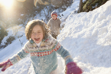 Boy and girl running in snow