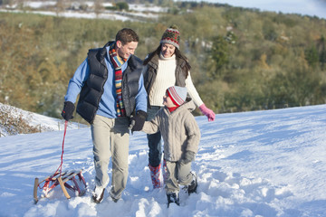 Family with sled walking in snowy field
