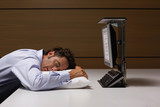 Businessman sleeping on pillow at desk