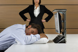 Angry businesswoman looking down at businessman sleeping on pillow at desk