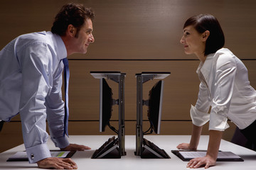 Smiling businessman and businesswoman leaning on desks face to face