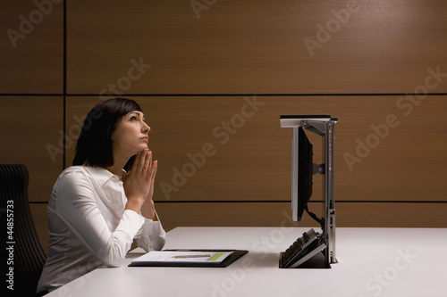 Businesswoman looking up with hands clasped at desk in office