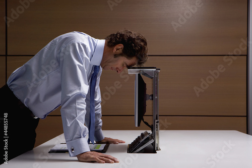 Frustrated businessman leaning on computer in office