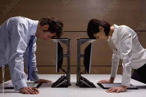 Businessman and businesswoman leaning on computers in office