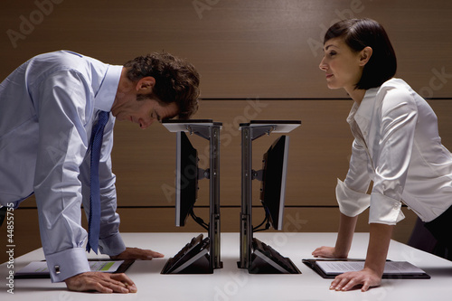 Businesswoman watching businessman lean on computer in office