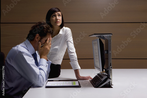 Worried businessman and businesswoman working at desk in office