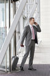 Businessman with suitcase talking on cell phone in airport