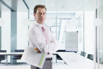 Portrait of confident businessman holding paperwork with arms crossed in conference room