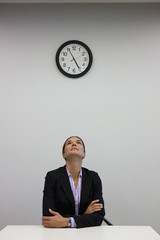 Businesswoman looking up at clock in office