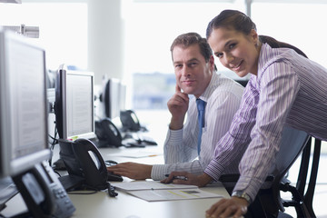 Portrait of smiling businessman and businesswoman at computer in office