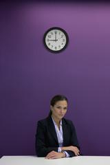 Portrait of serious businesswoman sitting at desk under clock