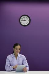 Businesswoman using digital tablet at desk under clock