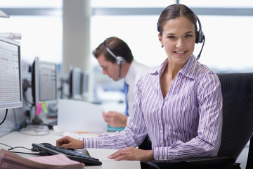 Portrait of smiling businesswoman wearing headset at desk in office
