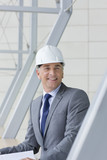 Smiling architect wearing hard hat and suit