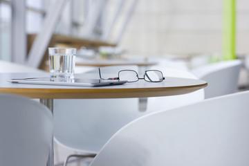 Digital tablet, eyeglasses and water on table
