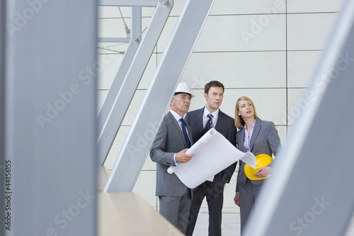 Architects and engineer holding blueprints in office