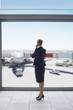 Businesswoman in suit talking on cell phone at airport window