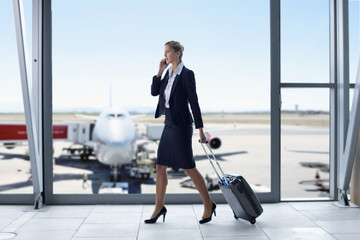 Businesswoman in suit pulling suitcase and talking on cell phone at airport window