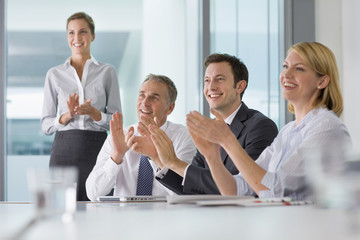 Smiling business people clapping in meeting