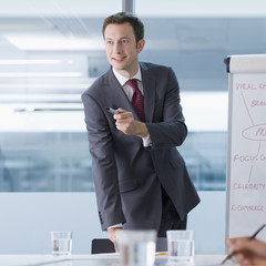 Smiling businessman leading meeting in conference room
