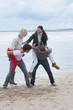 Young couples in piggyback battle on beach