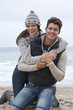Portrait of smiling young couple hugging on beach