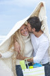 Portrait of smiling young couple with blanket and basket kissing under blanket on beach