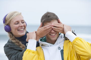 Young woman covering boyfriendճ eyes on beach