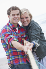 Portrait of smiling young couple playing tug-of war