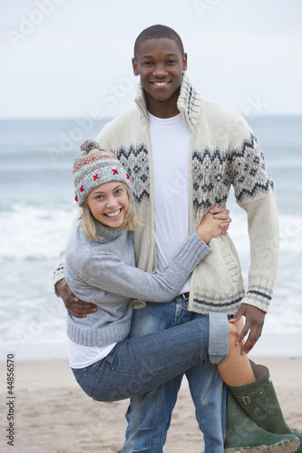 Portrait of young woman hanging from boyfriend on beach