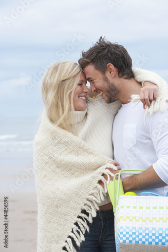 Smiling couple with blanket and basket hugging face to face on beach