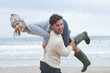 Portrait of young man carrying girlfriend over shoulder on beach