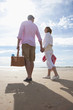 Young couple holding hands and walking with picnic basket on sunny beach