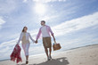 Couple holding hands and walking with picnic basket on sunny beach