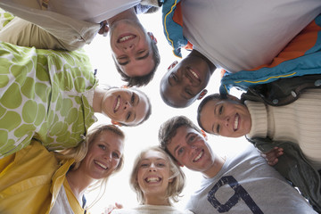 Low angle portrait of smiling friends in huddle