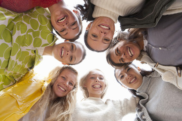 Low angle portrait of smiling young women in huddle