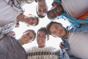 Low angle portrait of smiling young men in huddle