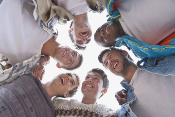 Low angle portrait of laughing young men in huddle